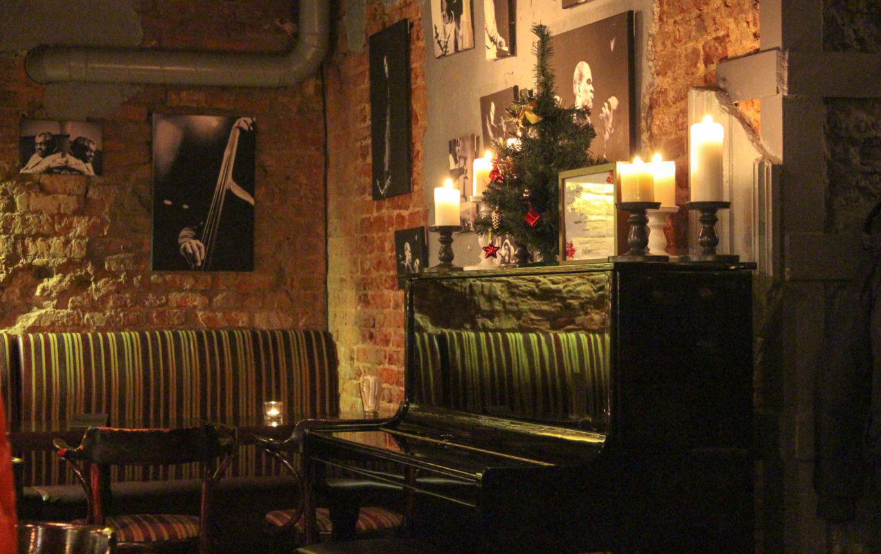 Ein Pianino mit Kerzen drauf, darüber eine Lenin-Foto