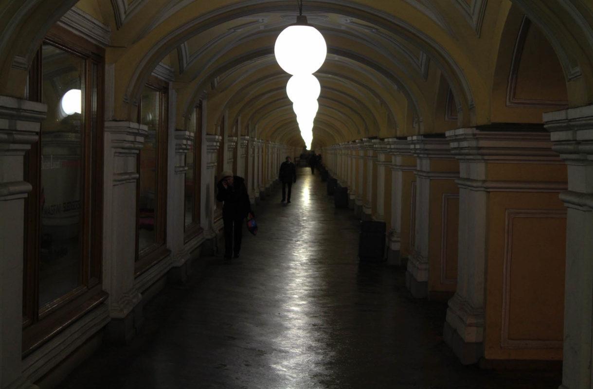 Ein öffentlicher Durchgang mit Hängelampen, die sich am Boden spiegeln